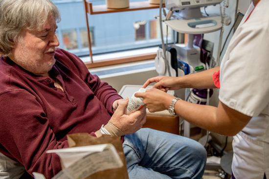 纪念斯隆-凯特琳癌症中心肿瘤科医生在给一名参加临床试验的患者检查身体